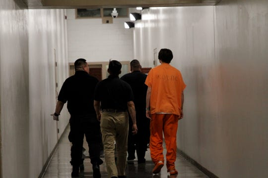 A detainee and detention center workers push trays, Tuesday, Jan. 28, 2020, through a hall at the San Juan County Adult Detention Center.