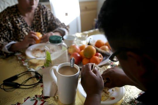 Rafael Campos y su madre desayunan dentro de su casa rodante alquilada en Thousand Palms, California, el domingo 26 de enero de 2020.