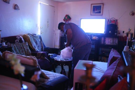 Rafael Campos limpia la sala dentro de su casa rodante alquilada en Thousand Palms, California, el domingo 26 de enero de 2020.
