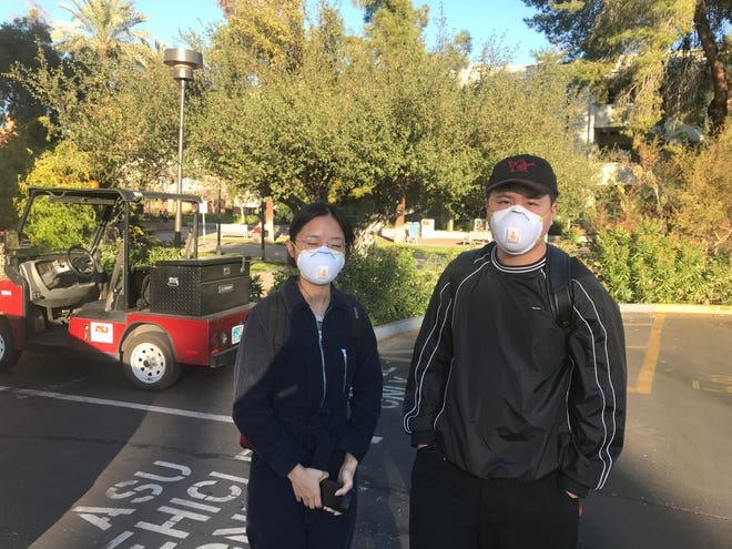 Arizona State University students Huijia Lin (left) and Yuxin Lu wear masks to protect themselves from the new coronavirus on Jan. 27, 2020, in Tempe.