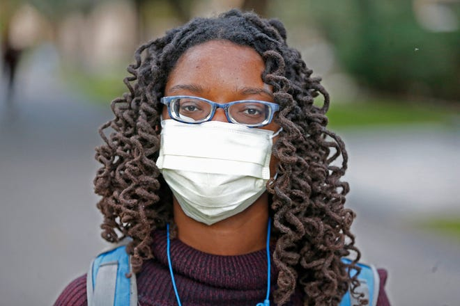 Daba Yague wears a mask as she walks between classes after a confirmed case of the new coronavirus was reported on ASU's Tempe campus on Jan. 26, 2020.