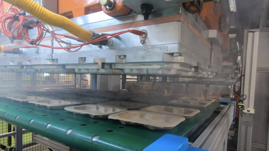 Machines press out compostable meat packaging containers made Arizona-based Footprint.