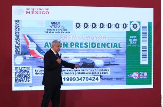 El presidente de México Andrés Manuel López Obrador muestra el potencial boleto de la rifa del avión presidencial.