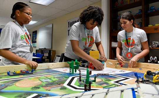 Armani Hill, 13 at left, Jahziah Ford, 12, and Cheyenne Minichino, 12 right, of the RoboThinkers youth robotics team set up their robot for a run,  Monday, January 26, 2020. The team recently placed first place in Programming and fifth in points during the Robot Games in Reading.John A. Pavoncello photo