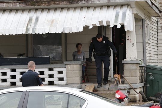 Officer Matt Smith walks a dog to a neighbor's residence as a handcuffed Linda Sue Allen sits on her porch Tuesday morning after the Wayne County Drug Task Force served her with an arrest warrant in the 200 block of South 12th Street.