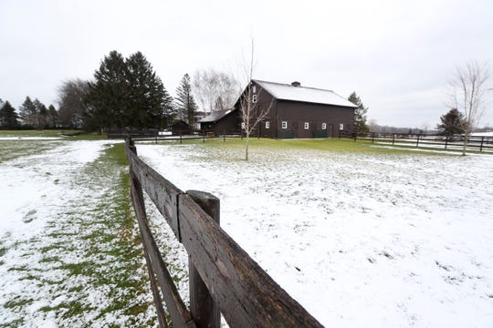 A large pasture leads to a barn on the property.