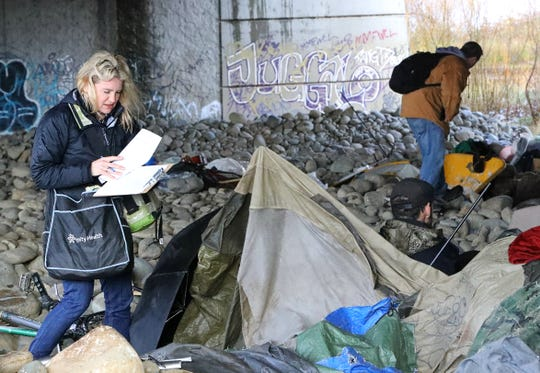 Volunteers Jennifer Powell, left, and Brandon Thornock interview homeless people under the Cypress Avenue bridge in Redding during the annual Point-in-Time count on Tuesday, Jan. 28, 2020. Results from the survey are tied to housing funding from the U.S. Department of Housing and Urban Development.