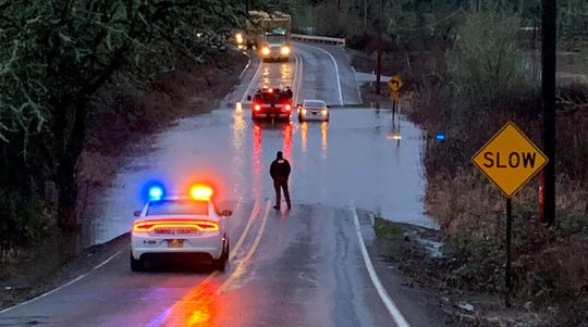 A Battalion Chief's vehicle pulls aside a car stalled in high water on SW Bellevue Highway Tuesday morning.