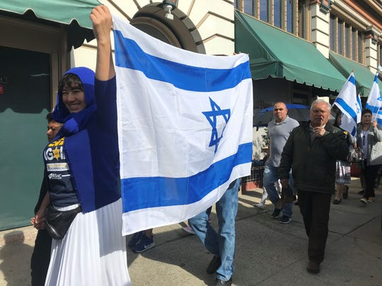 A woman held up the blue and white flag of Israel as she marched through Oldtown Jan. 25, 2020 to remember the more than 6 million Jews killed in the Holocaust.