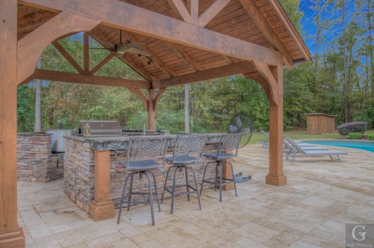 A free standing kitchen is made of flagstone and rustic beams