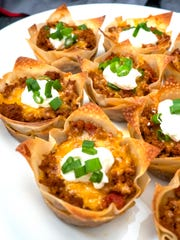 Taco filling is layered with melted cheese in crispy wonton wrappers for Tasty Taco Cups.