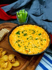 Cheesy Buffalo Chicken dip in a cast iron skillet is hot Super Bowl snack.