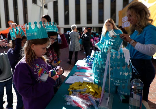 Students line up to get paper crowns and other goodies from a booth during Children's Day at the Capitol on Tuesday, Jan. 28, 2020.