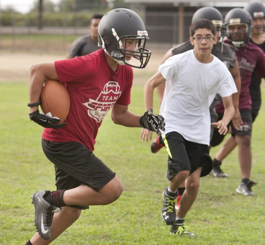 Brian Barajas runs with the football during football practice at Orosi High School. Photo taken on Wednesday, August 5, 2015.
