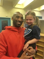Kobe Bryant holds Brynn Downer, the daughter of his high school basketball coach, Gregg Downer.