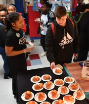 Chartwells K12 dietician Sarene Glenn tells a Hirschi High student how to vote for their pick between a pulled pork barbecue and bahn mi Asian sandwich during a Student Choice event Tuesday.