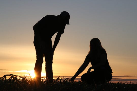 """Wisconsin photojournalist Harlen Persinger's photo """"Solid Foundation"""" features a farm couple checking out a corn field in the sun's fading light."""