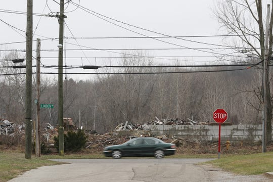 A car drives past the ruins of the former Lear building on Linden Avenue. The Muskingum County Land Reutilization Corporation, better known as the land bank, is back in business, and has started to look for ways to acquire the property in hopes of having it cleaned up.