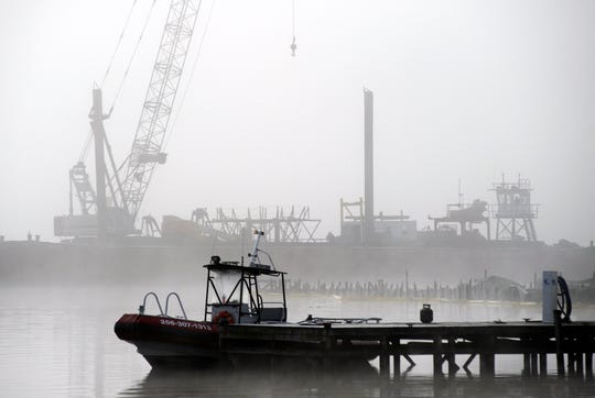 A salvage crane shrouded in fog rises above a barge in a creek near the Tennessee River at the scene of a fatal marina fire at Scottsboro, Ala., on Tuesday, Jan. 28, 2020.