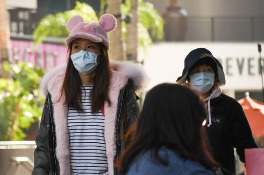Tourists wear surgical masks while visiting the Hollywood & Highland mall in Los Angeles Monday. There are five confirmed U.S. cases of coronavirus.