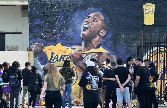 Fanáticos se reúnen para llorar la muerte de la leyenda de la NBA Kobe Bryant frente a un mural cerca del Staples Center en Los Ángeles.