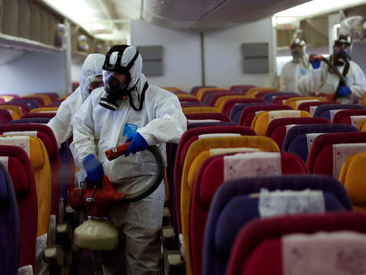 Thai technicians wearing protective suits spray disinfectant on passenger seats aboard a Thai Airways International aircraft during a campaign which steps up measures to investigate and prevent the spread of the coronavirus at the Aircraft Hangar of Thai Airways Technical Department near Suvarnabhumi Airport in Samut Prakan province, Thailand, 28 January 2020.
