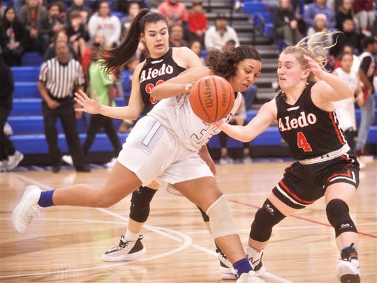 Cooper's Jennika Willis (32) tries to get past Aledo's Riley Sale (4) and Addyson Hebel in the second half. Cooper beat the Ladycats 37-30 in the District 4-5A game Tuesday at Cougar Gym.