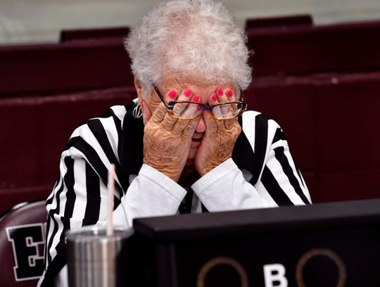 Scorekeeper Mary Mosley covers her eyes in embarrassment between games at Eula High School as people gather around her table to honor her Jan. 24. The gym was renamed Mary Mosley Gymnasium to honor her years of volunteer service there.