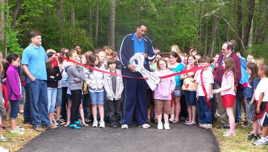 Town of Black Mountain alderman Carlos Showers cut the ribbon at the official opening of the Flat Creek Greenway on April 26., 2011. Students from Black Mountain Elementary joined him.