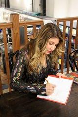 Mindie Barnett signs copies of her memoir.