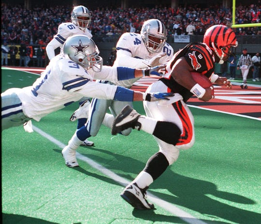 Text: 1997.1214.09.1-BENGALS-ERICTD-Bengal halfback Eric Bieniemy turns the corner on a 20 yard second quarter touchdown pursued by Cowboy defenders Brock Marion #31 and Omar Stoutmire #24. The touchdown made the score 10-9, tied 10-10 when the point after was made. patrick reddy/the cincinnati enquirer/pr
