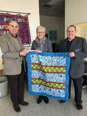 Pictured at the delivery ofthe $1,000 check areAndrew Casella, Knights of Columbus; Pam Fox, director,Quilts for Kids;and Tom Monroe, Knights of Columbus.