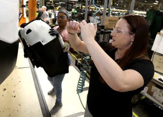 Peltier gives advice earlier this month about lifting parts with Dianne Henderson, 66, a line worker at the General Motors Lansing Delta Township Assembly Plant in Delta Township.