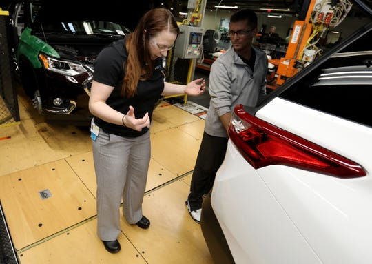 Douglas James, 32, of Windsor Township, Michigan, looks on and gets advice from Corinne Peltier at the General Motors Lansing Delta Township Assembly Plant.