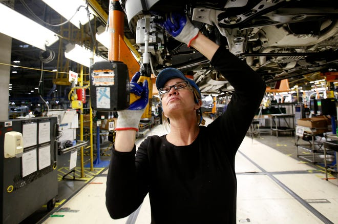 Penny Snow, 47, of Charlotte, Michigan works at adding screws underneath a Chevrolet Traverse at the General Motors Lansing Delta Township Assembly Plant in Delta Township, Michigan on Thursday, Jan. 16, 2020.