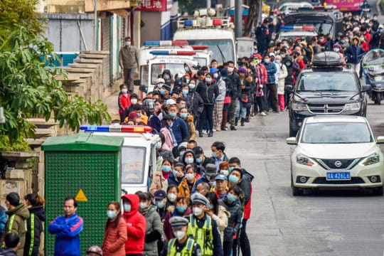 People line up to buy face masks from a medical supply company in Nanning in southern China's Guangxi Zhuang Autonomous Region, Wednesday.