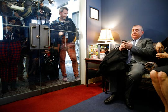 Lev Parnas, a Rudy Giuliani associate with ties to Ukraine, looks at his phone as he waits in the office of Senate Minority Leader Sen. Chuck Schumer of N.Y., during the impeachment trial of President Donald Trump.