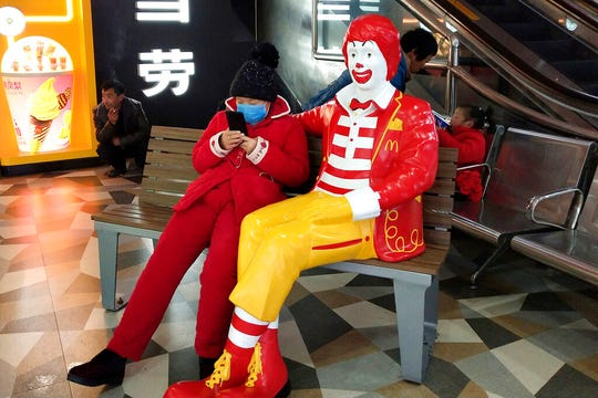 A woman wears a face mask and she uses her smartphone as she sits next to a statue of Ronald McDonald at a McDonald's restaurant in Suzhou in eastern China's Jiangsu Province, Sunday, Jan. 26, 2020.