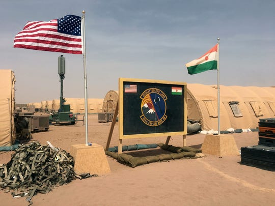 FILE- In this file photo taken Monday, April 16, 2018, a U.S. and Niger flag are raised side by side at the base camp for air forces and other personnel supporting the construction of Niger Air Base 201 in Agadez, Niger.
