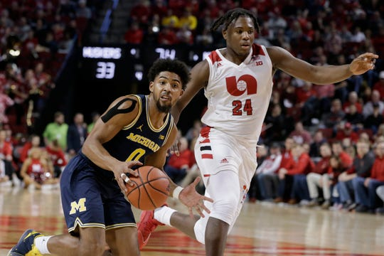 Michigan's David DeJulius drives around Nebraska's Yvan Ouedraogo.