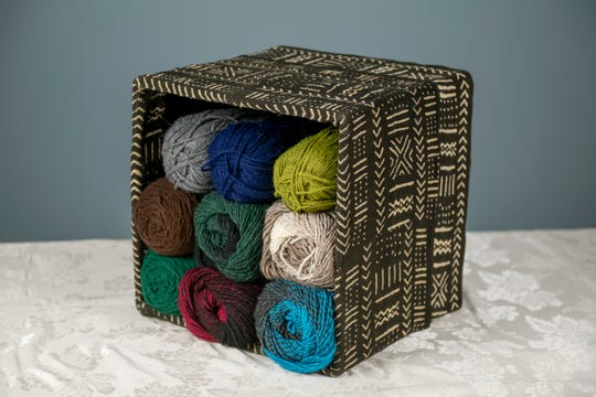 A collapsable box that has been upholstered with handwoven mudcloth can now be used as an ottoman or decorative storage.