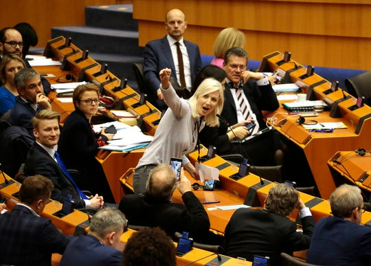 MEP from Finland Laura Huhtasaari, center, speaks ahead of a vote on the UK's withdrawal from the EU, the final legislative step in the Brexit proceedings, during the plenary session at the European Parliament in Brussels, Wednesday, Jan. 29, 2020.