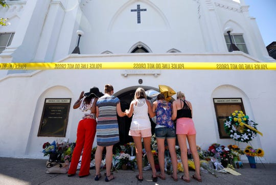 FILE - In this June 18, 2015, file photo, a group of women pray together at a makeshift memorial on the sidewalk in front of the Emanuel AME Church in Charleston, S.C.