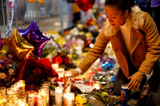 Angelica Diaz places a candle at a memorial for Kobe Bryant near Staples Center Tuesday in Los Angeles.