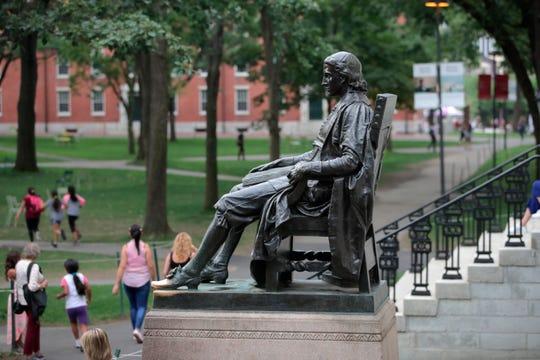 FILE - In this Aug. 13, 2019, file photo, the statue of John Harvard sits in Harvard Yard at Harvard University in Cambridge, Mass.