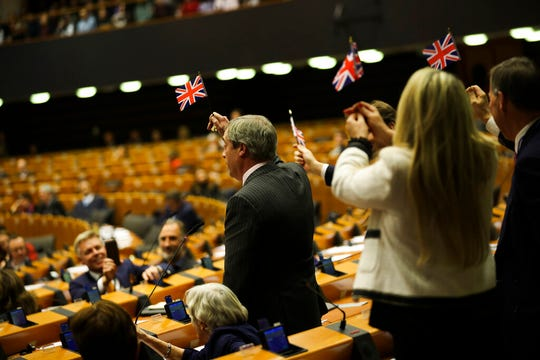 British European Parliament member Nigel Farage, left, and other pro-Brexit British MEP's wave the Union flags during the plenary session at the European Parliament in Brussels, Wednesday, Jan. 29, 2020.