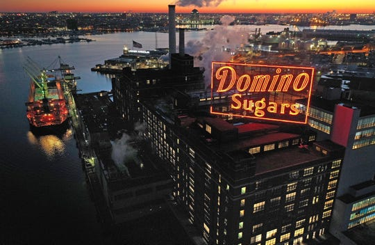 Domino Sugar's iconic neon sign glows at sunrise Wednesday morning. Domino is among the small number of U.S. refineries seeing an increase in imported sugar due to the terrible domestic harvests of sugar beets and sugar cane last year.