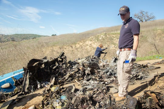 NTSB investigators Adam Huray, right, and Carol Hogan examine wreckage as part of the NTSB's investigation of a helicopter crash near Calabasas, Calif. on Monday.  The Sunday crash killed former NBA basketball player Kobe Bryant, his 13-year-old daughter, Gianna, and seven others .