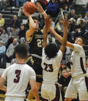 Aidan Chamberlin of Corning goes up for a shot in between two Elmira defenders during the Express' 65-38 win in boys basketball Jan. 28, 2020 at Elmira High School.