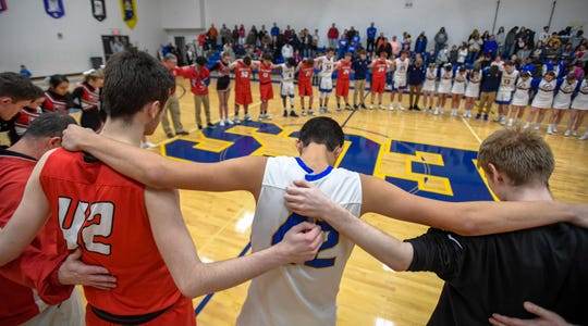 Birds of a feather, Eagles and Cardinals gather in prayer following the game as the Evansville Christian Eagles plays the Washington Catholic Cardinals in Evansville Tuesday evening, January 28, 2020.